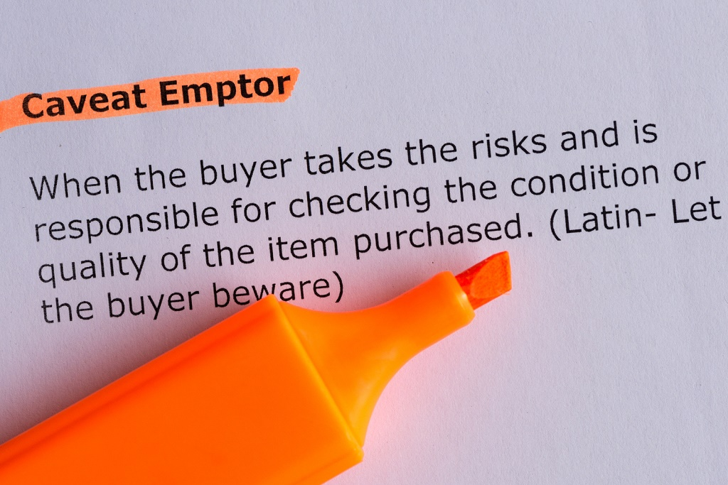 caveat emptor word highlighted on the white paper