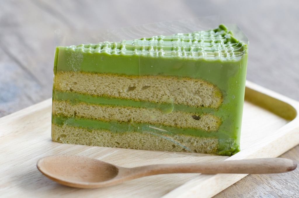 Green tea cake and spoon on wooden plate, green