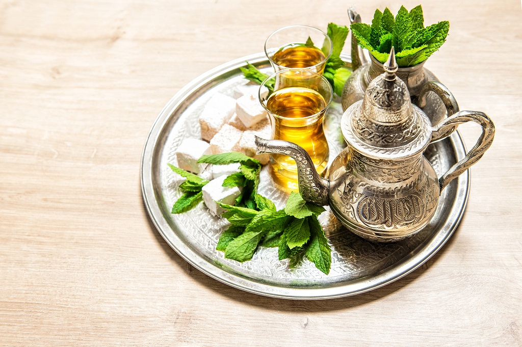 Tea with mint leaves and traditional turkish delight. Oriental hospitality concept. Holidays table setting. Ramadan kareem