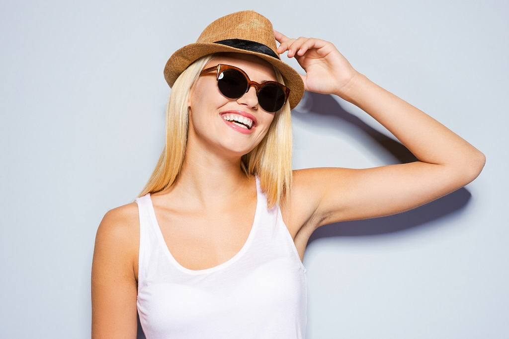 Beautiful young blond hair women adjusting her hat and smiling while standing against grey background