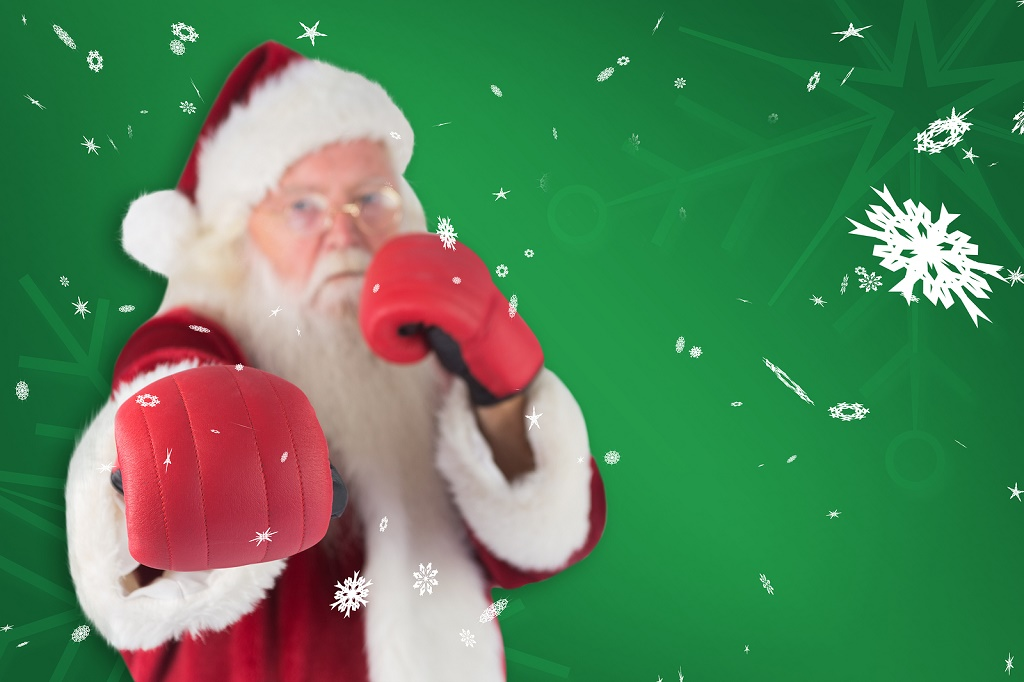 Santa Claus punches with his right against green snowflake background
