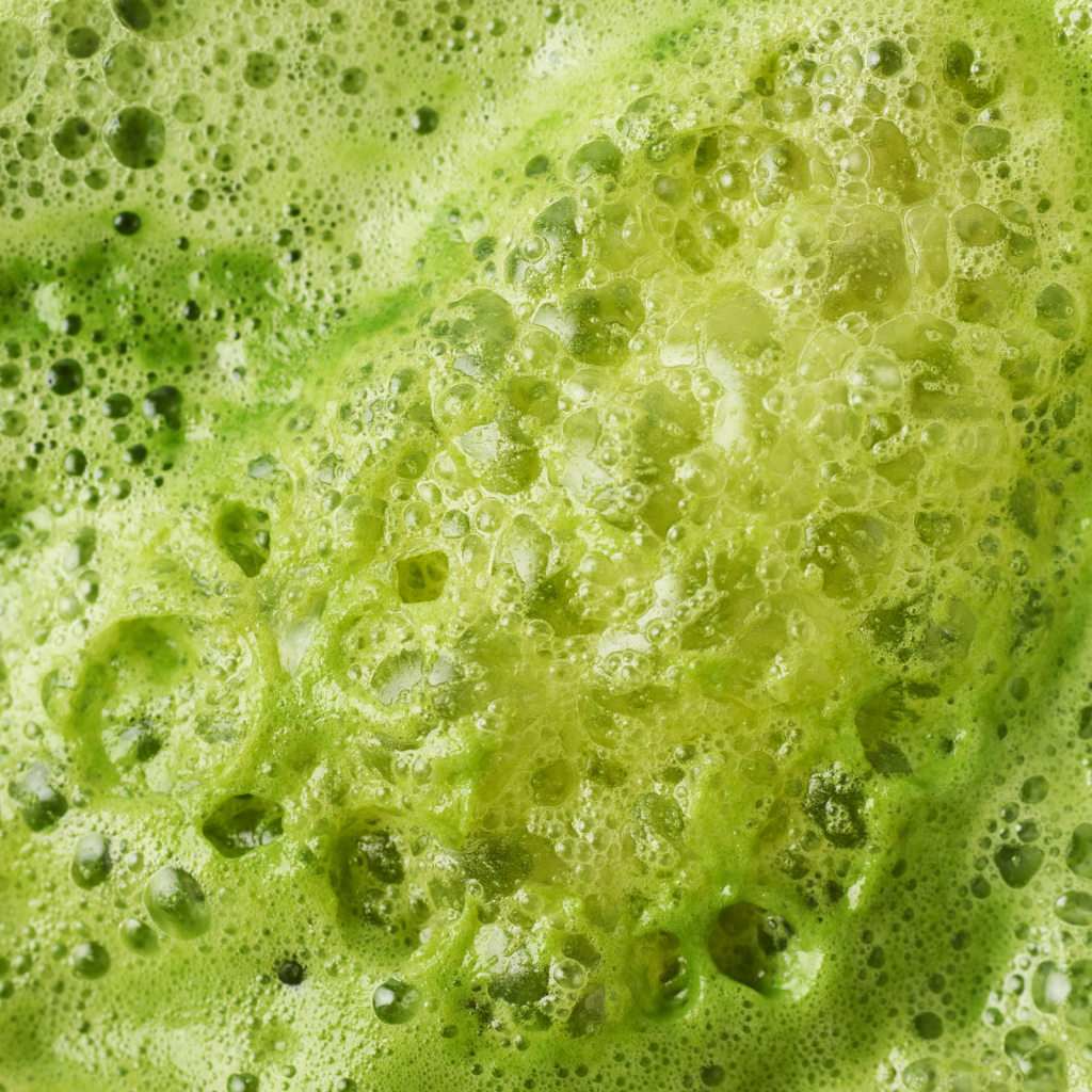Green juice foam close-up shot as a background texture composition