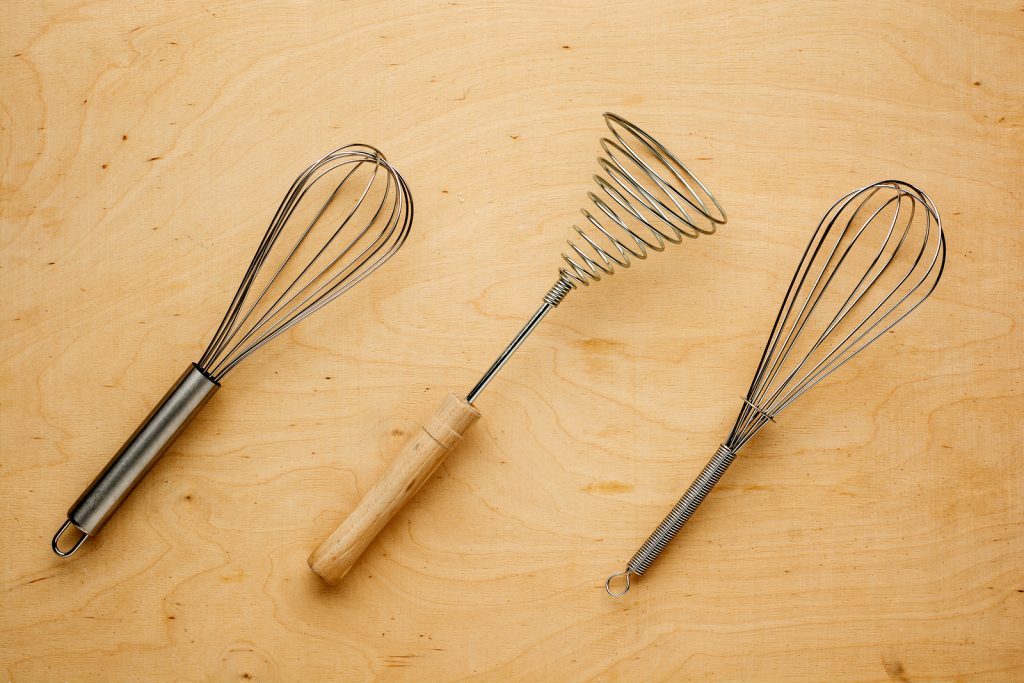 Metal whisk or eggbeater for whipping and whisking cooking ingredients lying on a textured wooden background.